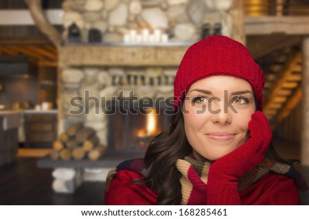 Smiling, Comfortable Mixed Race Girl Looking To The Side Enjoying Warm Fireplace In Rustic Cabin. - stock photo