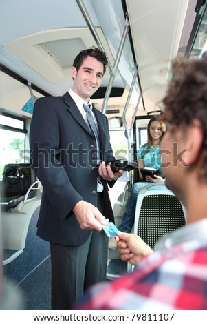 Smiling conductor checking tickets on a tram - stock photo