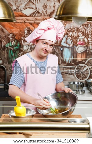Smiling confectioner, wearing in pink apron, hat and striped shirt, holding green corolla, metallic bowl, and knead the dough for gingerbread, on the wooden board, in the kitchen with paintings