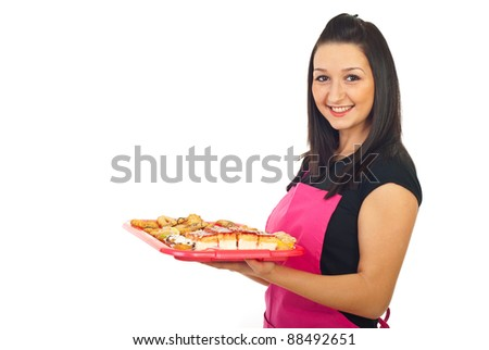 Smiling confectioner woman holding cookies and standing in semi profile isolated on white background - stock photo