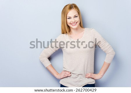 Smiling confidence. Beautiful young women looking at camera and posing while standing against grey background   - stock photo