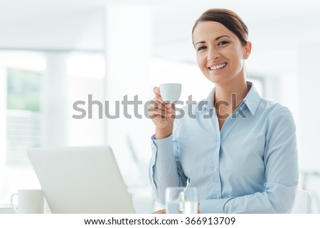 Smiling confident business woman sitting at office desk and having a coffee break, she is relaxing and smiling at camera - stock photo