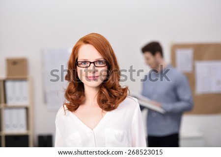 Smiling confident businesswoman or manageress with shoulder length red hair wearing glasses looking at the camera with a smile as her co-worker works in the background - stock photo