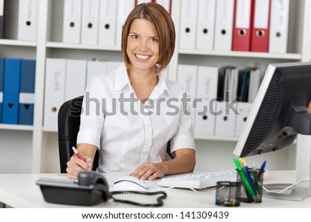 Smiling confident businesswoman sitting at her desk in the office in front of a desktop computer - stock photo