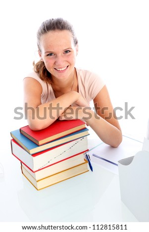 Smiling confident college student Smiling confident young college student seated at her desk with a pile of textbooks for her studies - stock photo