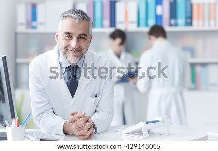 Smiling confident doctor at the reception desk, medical staff working on the background - stock photo