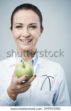 Smiling confident female nutritionist holding an apple - stock photo