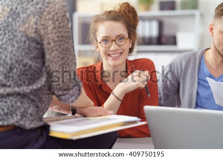 Smiling confident friendly young businesswoman sitting in a meeting with office colleagues looking at the camera with a beaming smile - stock photo