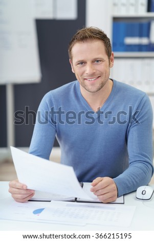 Smiling confident handsome young businessman sitting at his desk in the office doing paperwork - stock photo