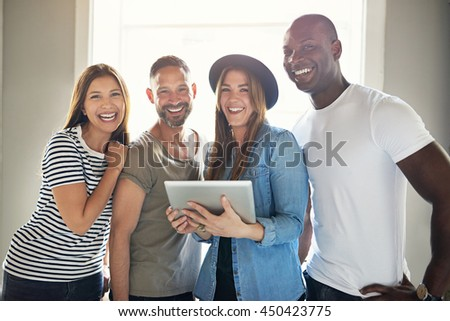 Smiling confident informal young group of multiracial businesspeople standing grouped around a tablet computer laughing and smiling at the camera - stock photo