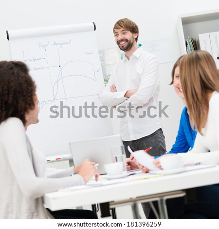 Smiling confident male team leader giving a presentation to his colleagues as they sit taking notes and brainstorming with him - stock photo