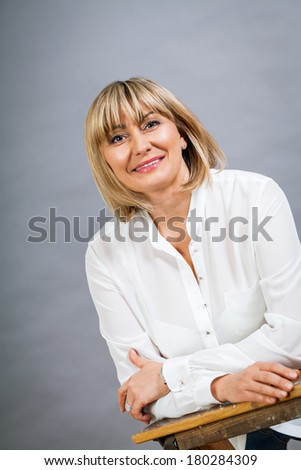 Smiling confident middle-aged blond woman in a fresh white blouse standing with her hand on her hip smiling at the camera, on grey
