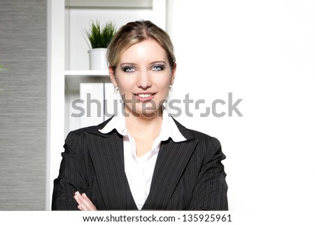Smiling confident professional woman standing in her office looking at the camera with her arms folded - stock photo