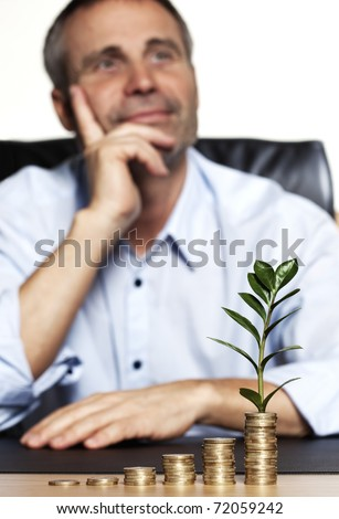 Smiling confident senior businessman sitting at desk in front of increasing stacks of coins with growing green plant, looking forward to developing business growth. - stock photo