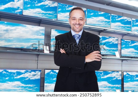 Smiling Confident Storekeeper Standing In Television Store - stock photo
