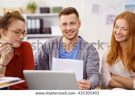 Smiling confident young businessman in a meeting flanked by two young women co-workers sitting at a laptop holding a paper document - stock photo