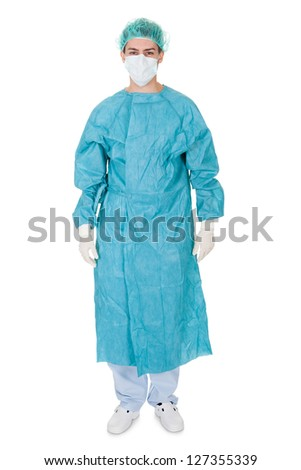 Smiling confident young surgeon wearing a gown and stethoscope standing isolated on white