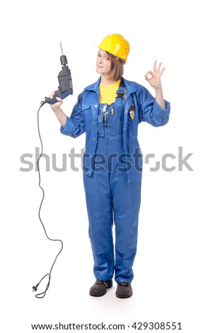 smiling construction female worker in yellow helmet and blue workwear with drill showing an okay sign isolated on white background. proposing service. advertisement gesture