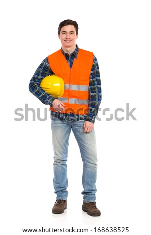 Smiling construction worker in orange waistcoat and yellow helmet under his arm.  Full length studio shot isolated on white. - stock photo