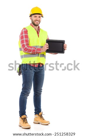 Smiling construction worker in yellow helmet and lime waistcoat holding shockproof digital tablet. Full length studio shot isolated on white.