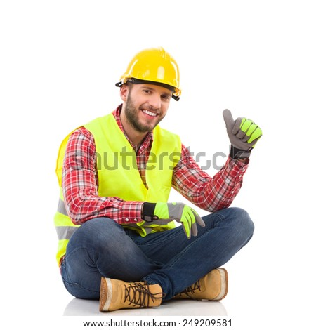 Smiling construction worker in yellow helmet and lime waistcoat sitting on the floor with legs crossed and showing thumb up. Full length studio shot isolated on white. - stock photo