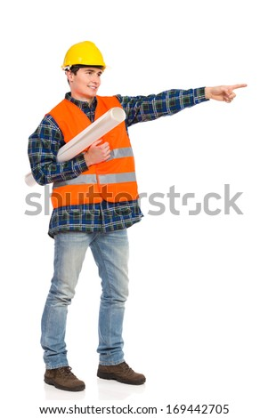 Smiling construction worker in yellow helmet and reflected orange waistcoat pointing. Full length studio shot isolated on white. - stock photo