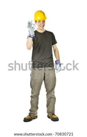 Smiling construction worker showing okay sign standing isolated on white background - stock photo