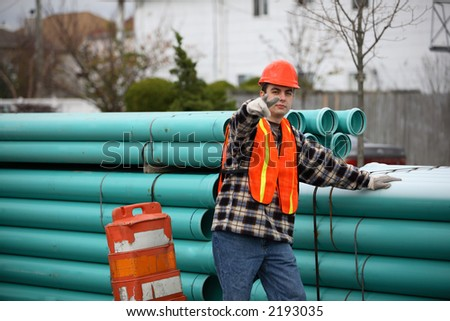 Smiling construction worker standing next to big pile of pipes, pointing at the viewer.