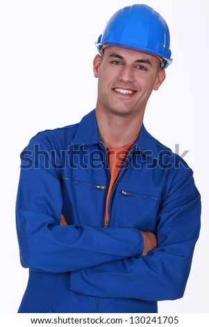 smiling construction worker with folded arms - stock photo