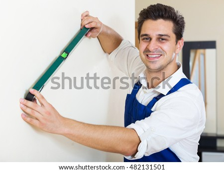 Smiling constructor smoothing the wall surface indoors
