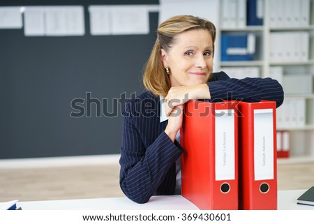 Smiling contented middle-aged businesswoman sitting at her desk resting her chin on two red binders looking at the camera with a friendly smile, with copy space - stock photo
