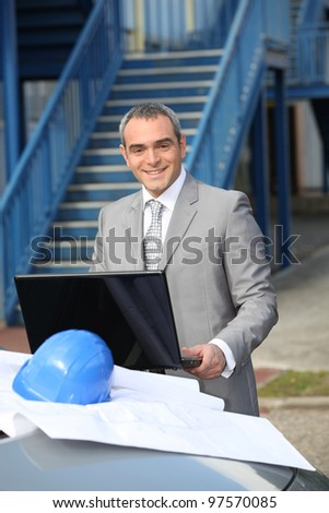 Smiling contractor standing outdoors - stock photo