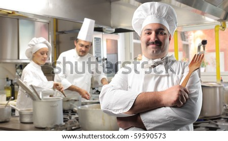 Smiling cook with two other cooks on the background - stock photo