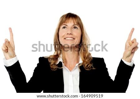 Smiling corporate lady pointing upwards - stock photo