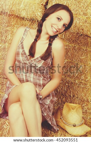 Smiling country girl in hay - stock photo