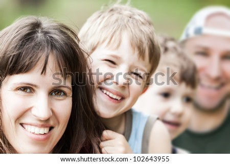 Smiling couple and little sons - family happiness - stock photo