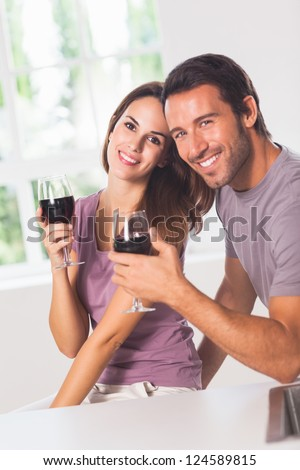 Smiling couple at the camera with wine - stock photo