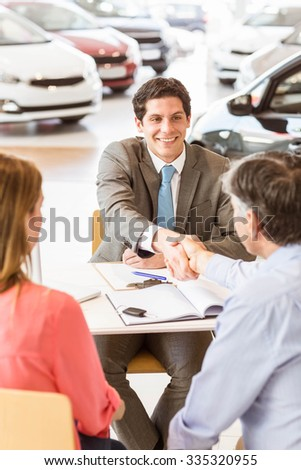 Smiling couple buying a new car at new car showroom - stock photo