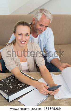 Smiling couple calculating their bills at the couch at home in the living room - stock photo