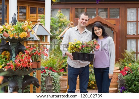 Smiling couple carrying tray of plants in garden center
