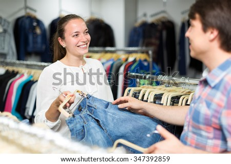 Smiling couple choosing blue jeans in a clothes store