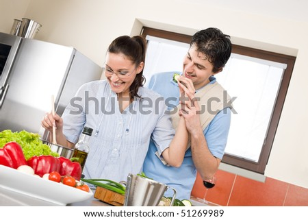 Smiling couple cook in modern kitchen with vegetables - stock photo