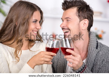 Smiling couple dating and drinking red wine at home - stock photo