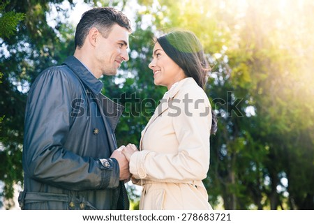 Smiling couple dating and flirting in park - stock photo