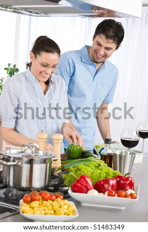Smiling couple drink red wine cooking in kitchen with vegetables - stock photo