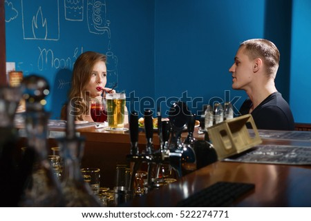 Smiling couple drinking beer in a bar