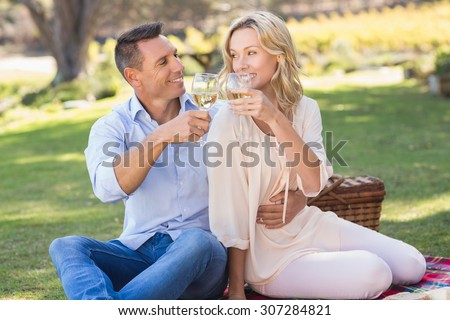 Smiling couple drinking wine and toasting in parkland
