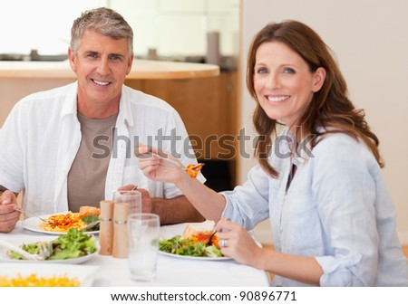 Smiling couple eating dinner together - stock photo