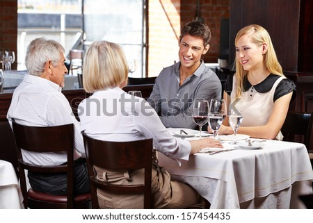 Smiling couple eating out with grandparents in a restaurant