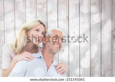 Smiling couple embracing and looking against light circles on grey background